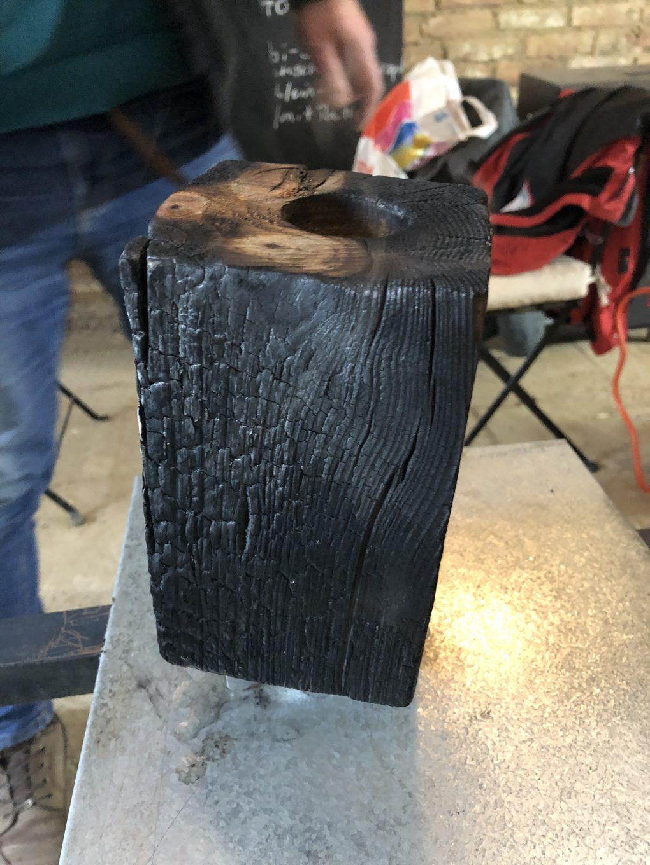 Ein Holzstück wird in der Shou Sugi Ban-Technik bearbeitet