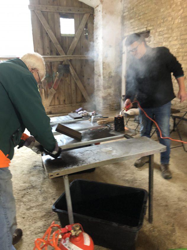 Teilnehmer flämmen Holzzuschnitte